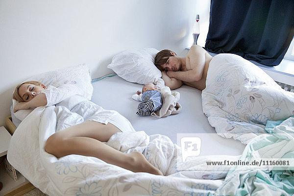 Eltern mit Neugeborenem im Bett liegend