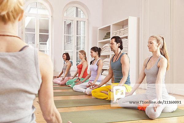 Gruppe von Menschen im Yoga-Studio sitzen in Lotus-Pose neben dem Lehrer
