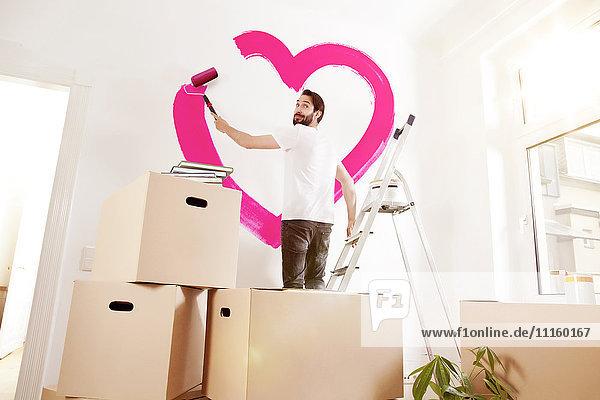 Junger Mann malt ein rosa Herz an einer Wand in neuer Wohnung Junger Mann malt ein rosa Herz an einer Wand in neuer Wohnung
