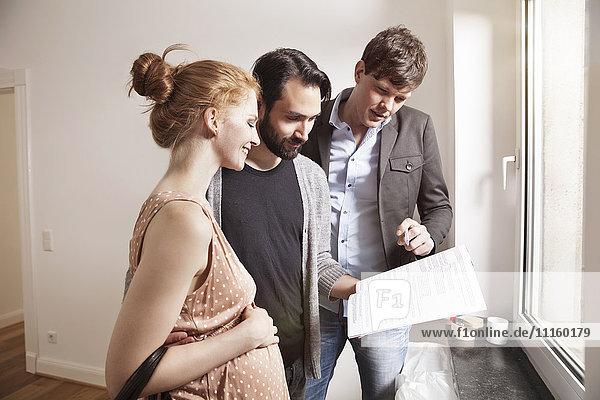 Immobilienmakler  der den werdenden Eltern einen Vertrag in einer neuen Wohnung zeigt.