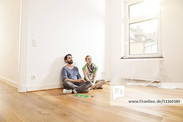 Junges Paar auf dem Boden sitzend in einer leeren Wohnung