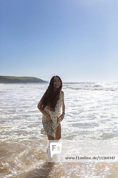 Lachende junge Frau im Wasser am Meer stehend