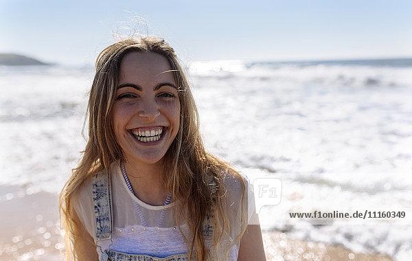 Porträt eines lachenden Teenagermädchens am Strand