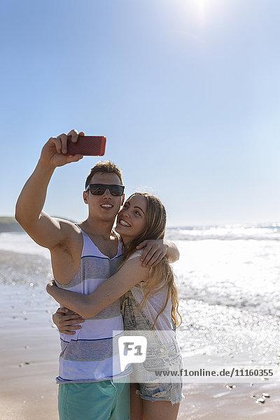 Verliebtes junges Paar  das sich am Strand vergnügt.