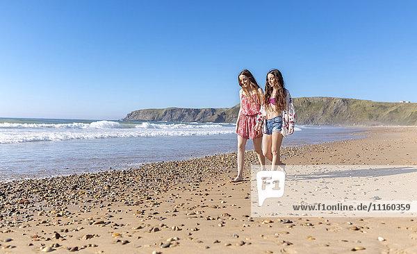 Zwei beste Freunde  die am Strand spazieren gehen.