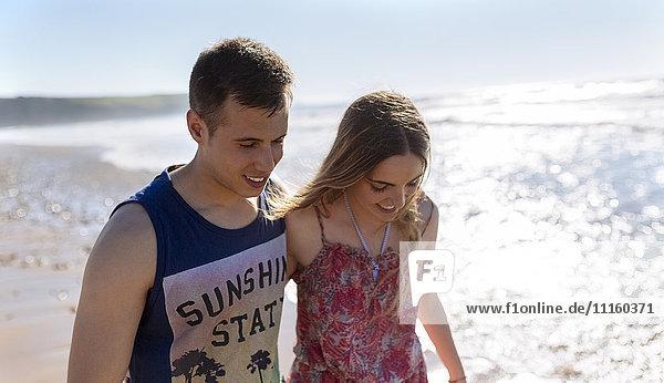 Ein glückliches junges verliebtes Paar  das am Strand spazieren geht.