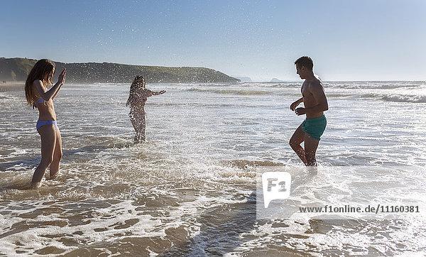 Drei Freunde  die sich am Strand amüsieren