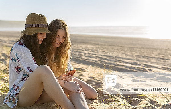 Two best friends sitting on the beach looking at smartphone