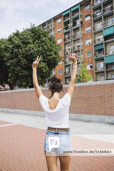 Rückansicht der jungen Frau beim Musikhören im Freien