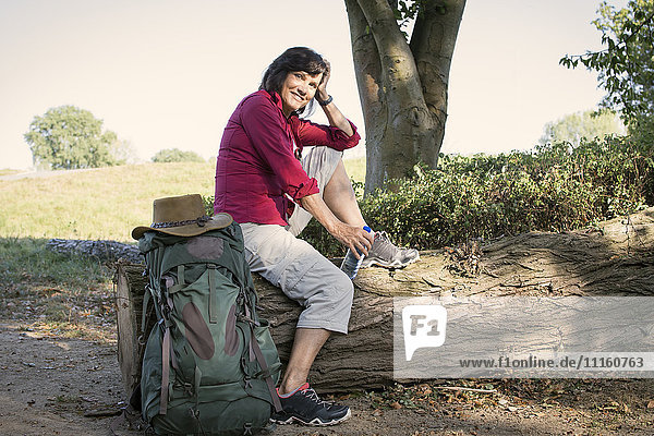 Senior woman with backpack resting on trunk