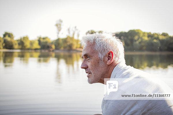 Serious senior man at a lake
