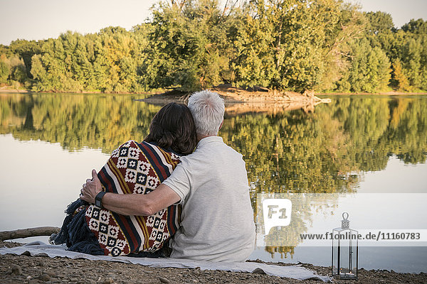 Relaxed senior couple at a lake in the evening