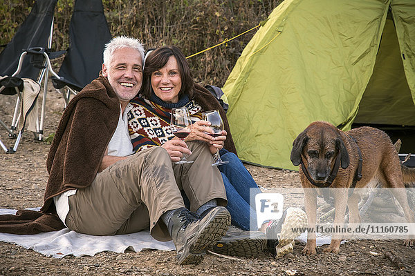 Happy senior couple with wine and dog at a tent