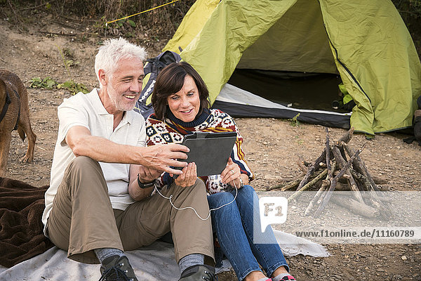Happy senior couple with tablet at a tent