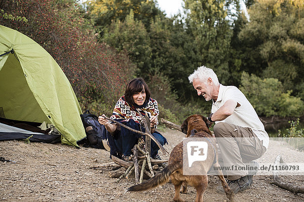 Senior couple with dog at a tent preparing a campfire