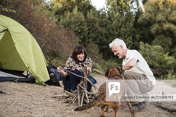 Seniorenpaar mit Hund am Zelt bei der Vorbereitung eines Lagerfeuers