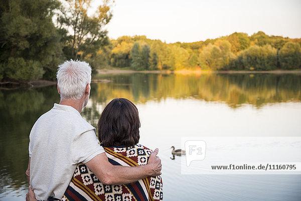 Senior couple at a lake looking at duck