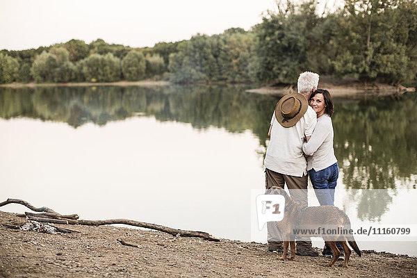 Senior couple with dog at a lake