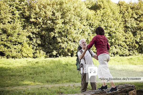 Seniorenpaar auf einer Wanderung auf Baumstamm balancierend