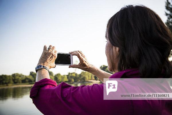 Senior woman at a lake taking pictures