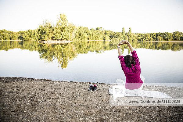 Senior woman stretching at a lake