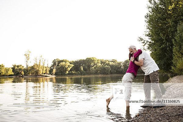 Senior couple hugging at a lake