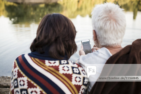 Senior couple with cell phone at a lake