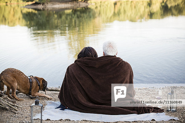 Relaxed senior couple with dog at a lake