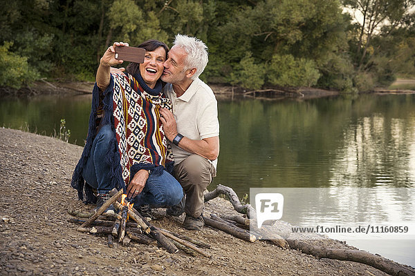 Happy senior couple at a lake taking a selfie at campfire