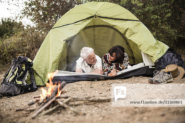 Happy senior couple lying in tent at campfire