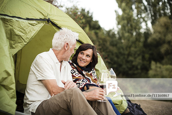 Senior couple sitting with wine in a tent