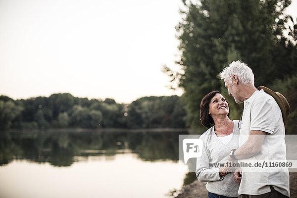 Smiling senior couple at a lake