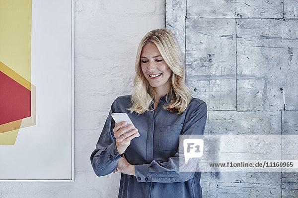 Lächelnde Geschäftsfrau beim Anblick des Smartphones