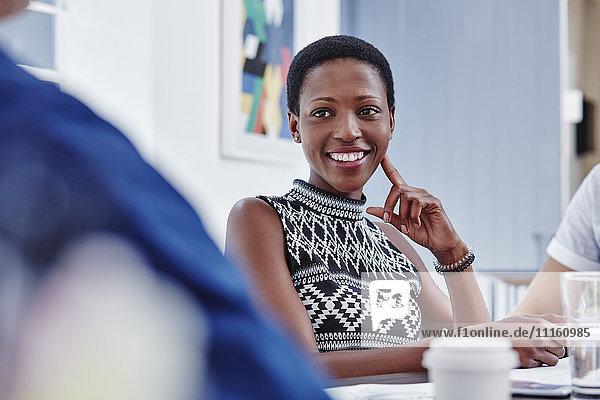 Lächelnde Frau in einer Besprechung mit Blick auf den Kollegen