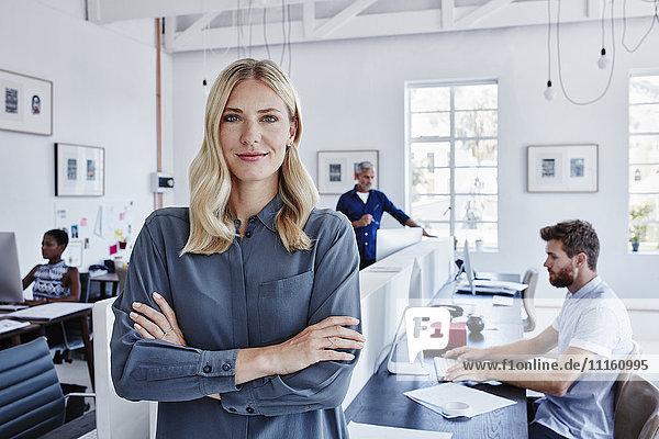 Porträt einer selbstbewussten Geschäftsfrau im Büro mit Mitarbeitern im Hintergrund