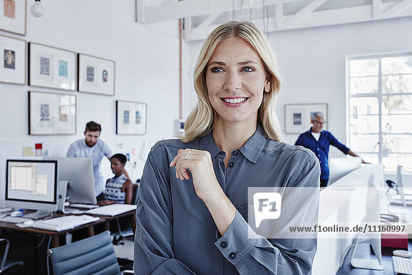 Lächelnde Geschäftsfrau im Büro mit Mitarbeitern im Hintergrund