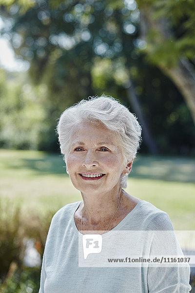 Portrait of smiling senior woman in park