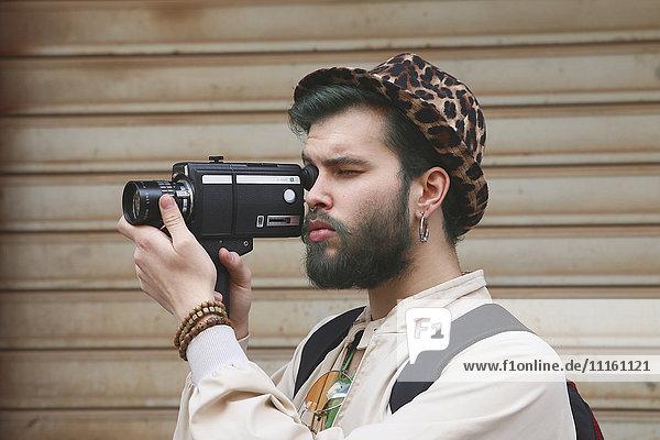 Junger Mann mit einer alten Videokamera