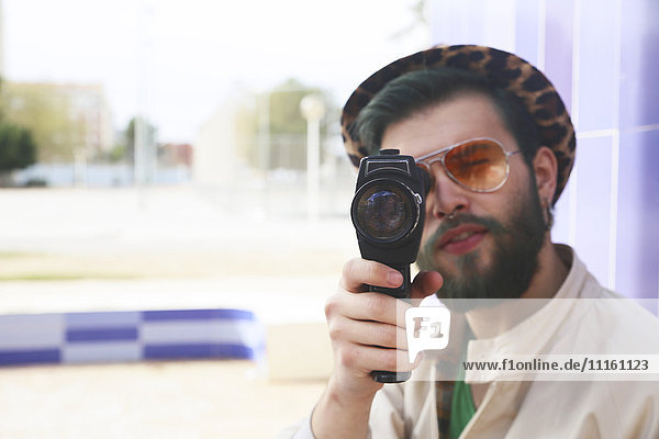 Young man using a vintage video camera