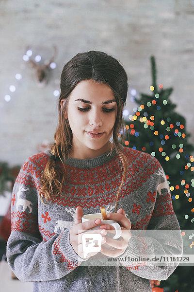 Porträt der Frau mit Tasse Kaffee zur Weihnachtszeit