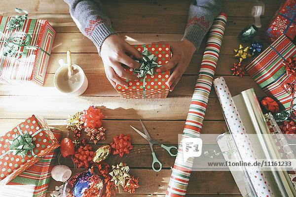 Frauenhände legen Krawatte auf Weihnachtsgeschenk