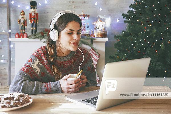 Frau mit Tasse Kaffee über Laptop und Kopfhörer zur Weihnachtszeit
