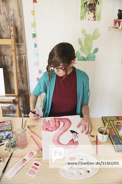 Frau malt Aquarell eines Flamingos auf dem Schreibtisch in ihrem Atelier