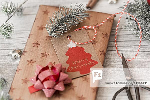 Weihnachtsschmuck  Scheren und verpackte Geschenke auf Holz