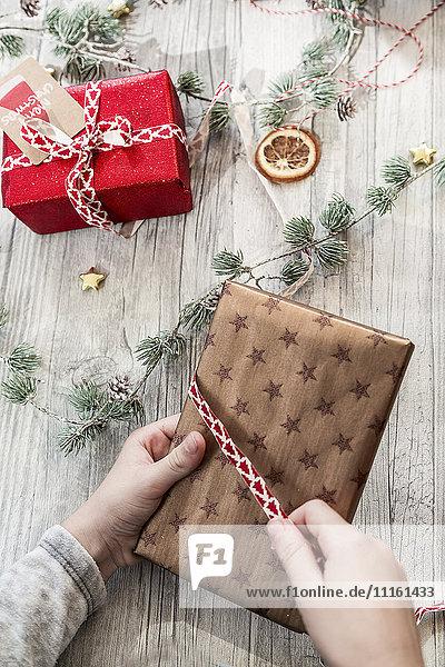Hände des Mädchens verpacken Weihnachtsgeschenk