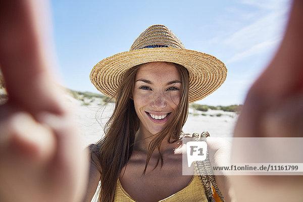Porträt einer lächelnden jungen Frau am Strand