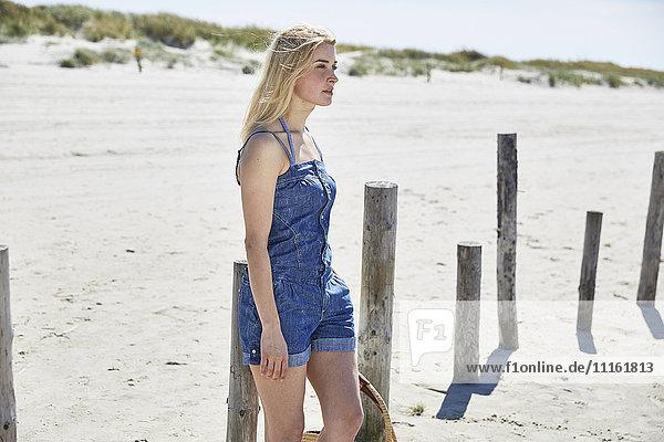 Junge Frau an Holzstangen am Strand