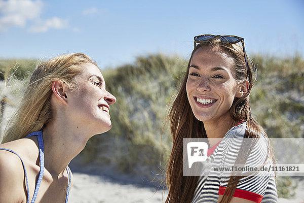 Zwei glückliche Freundinnen am Strand