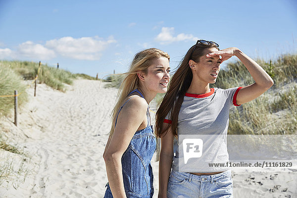 Zwei Freundinnen am Strand  die sich umsehen.