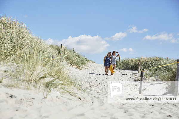 Zwei Freundinnen  die durch die Dünen zum Strand laufen